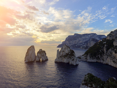 Faraglioni rocks towering up from bright blue Mediterranean waters on the island of Capri, Italy Stock Photo
