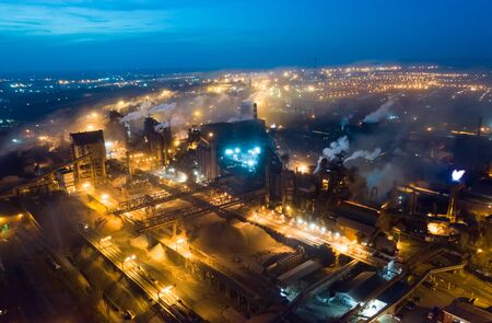 Aerial view. Emission to atmosphere from industrial pipes. Smokestack pipes shooted with drone. Night scene Stockfoto