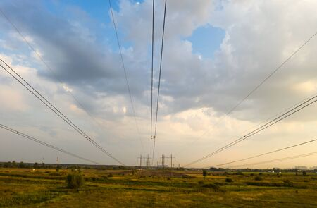 electricity pylons and high voltage power line at sunset.