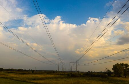 electricity pylons and high voltage power line at sunset. Background of beautiful cloudy sky.