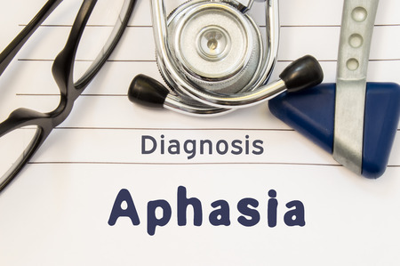 Neurological diagnosis of Aphasia. Neurological hammer, stethoscope and doctors glasses lie on doctor workplace on sheet of notebook, labeled with the title of medical diagnosis of Aphasia Stock Photo