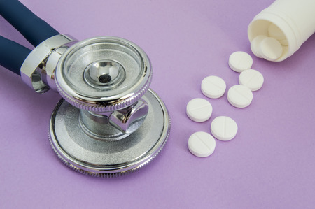 White pills falling out of a plastic tube or jar and the head of the stethoscope on a purple background. Frame or picture for to the internal medicine or cardiovascular direction