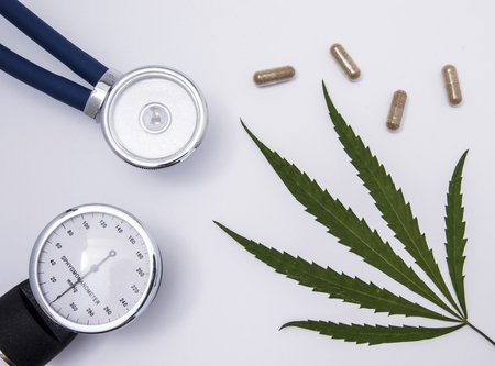 Stethoscope, sphygmomanometer and green leaf of medical cannabis with transparent capsules with herbal content on a white medical table.Use of medical marijuana in cardiology and internal medicine