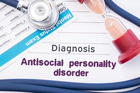 inattention: Diagnosis of Antisocial personality disorder (ASPD). On psychiatrist or psychologist table is paper with inscription Antisocial personality disorder near psychiatric report, hourglass and stethoscope Stock Photo