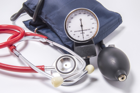 Set of diagnostic kit for determining increased blood pressure for doctors of cardiology, internal medicine, therapeutics, including red stethoscope, sphygmomanometer, bulb and inflated cuff close up Stock Photo