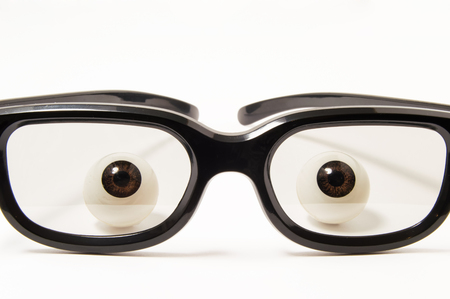 Figures eyes or eyeballs are behind black-rimmed glasses in a slightly darkened glass on a white background. Concept photo for ophthalmology, optometry, selection of glasses to correct or good vision Stock Photo