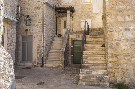 coquina: The courtyard of one of the houses in the Old Town of Budva, Montenegro, with stairs and old lantern