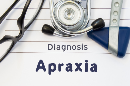 Neurological diagnosis of Apraxia. Neurological hammer, stethoscope and doctors glasses lie on doctor workplace on sheet of notebook, labeled with the title of medical diagnosis of Apraxia Stock Photo