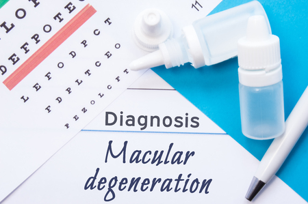 age related: Ophthalmology diagnosis Macular Degeneration. Snellen (eye) chart, two bottles of eye drops (medications) lying on note with inscription Macular Degeneration diagnosis in ophthalmologist office