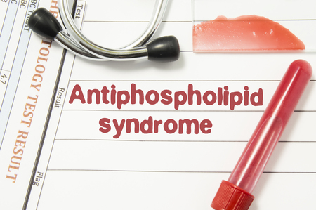 Diagnosis of Antiphospholipid Syndrome. Laboratory blood bottle, glass slide with blood smear, hematology test lying on note with printed text hematological diagnosis of Antiphospholipid Syndrome