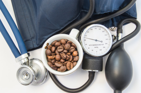 cuff: Caffeine and blood pressure. Small mug with coffee beans, symbolizing caffeine near sphygmomanometer, bulb, cuff and stethoscope top view. Concept effects of caffeine on heart rate and blood pressure