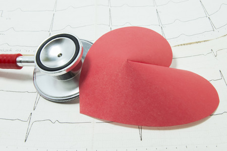 Red stethoscope and shape of red paper heart lie side by side on lines of printed ECG, symbolizing heart beat. Concept for diagnosis and treatment of heart disease in cardiology or internal medicine