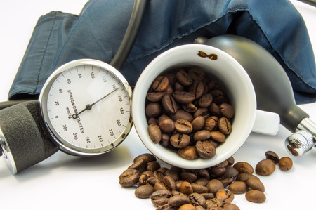 decaffeinated: Coffee and blood pressure. Cup with coffee beans inside, surrounded by cuff and sphygmomanometer for measuring blood pressure. Concept of influence and effects of coffee on low or high blood pressure