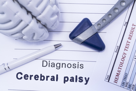 Diagnosis Cerebral palsy. Figure brain, neurological hammer, printed on a paper blood test and written diagnosis of Cerebral palsy in  medical form is lying on table in the doctor neurologist cabinet Stock Photo