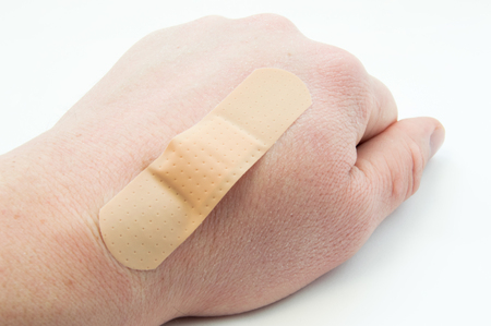 Wounded back of the wrist (cut, burn) and the wound is covered with plaster or band-aid. Use of first aid kit contents in patients with lesions of the skin or the primary wound treatment at the doctor