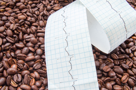 palpitations: Twisted type of electrocardiogram with printed ECG line lies on fried coffee beans. Impact coffee and caffeine on heart and heart rate, effects on palpitations and its force, development of disease