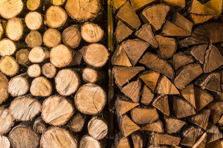 Round and triangular cutted or chopped firewood, folded in stacks in the storage, ready to use in fire, fireplace or campfire. Texture or background as wooden firewood Stock Photo