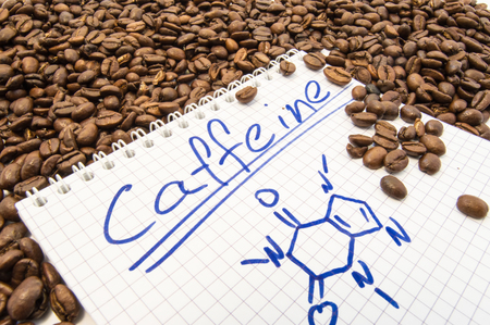 Notebook with text title caffeine and painted chemical formula of caffeine is surrounded by fried ready to use grains of coffee beans.