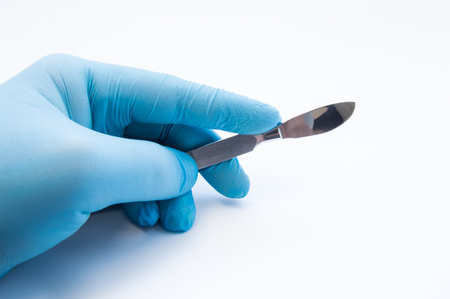 Hand holding scalpel. Palm of surgeon dressed in blue glove holding scalpel. Concept photo for surgeries, procedures, treatment, plastic surgery operation, work of surgical departments and hospitals Stock Photo
