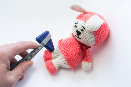 Doctor examines soft rabbit toy with neurological hammer and checks reflexes in feet. Concept for neurological examination of neurologist condition of nervous system children or infants in Pediatrics Stock Photo