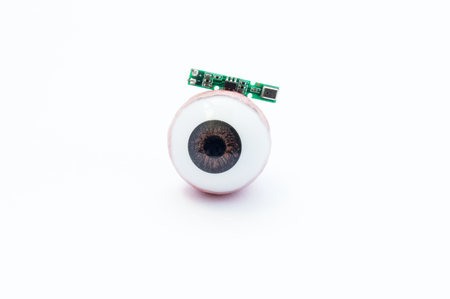 Anatomical model of human eye or eyeball with digital artificial microchip on white background. Treatment of vision loss, blindness, eye diseases using advanced digital bionic technology – implant