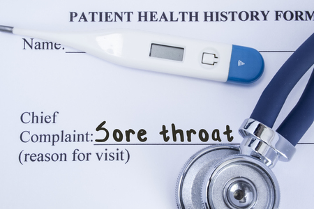 autograph: Chief complaint sore throat. Paper patient health history form, on which is written the complaint sore throat as the main reason for visit to the doctor, with a thermometer and stethoscope