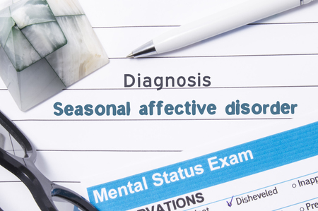 psychiatric: Psychiatric Diagnosis Seasonal Affective Disorder. Medical book or form with name of diagnosis Seasonal Affective Disorder is on table of doctor surrounded by questionnaire to determine mental state Stock Photo