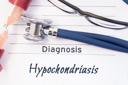 Diagnose Hypochondrie. Psychiatrische diagnose Hypochondriasis is geschreven op papier, waarop een stethoscoop en zandloper liggen om tijd te meten voor onderzoek. Conceptenfoto voor psychiatrie of psychologie