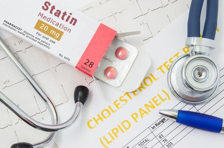 """Efectos y tratamiento de estatinas concepto foto. El envase abierto con tabletas de fármacos, en el que está escrito """"Statin Medication"""", se encuentra cerca de estetoscopio, análisis de resultados sobre el colesterol (panel de lípidos) y ECG Foto de archivo - 85215501"""