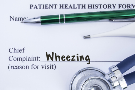 Complaint of wheezing. Paper health history form, which is written on the patients chief complaint of wheezing, surrounded by a stethoscope, electronic thermometer and a green ball-point pen