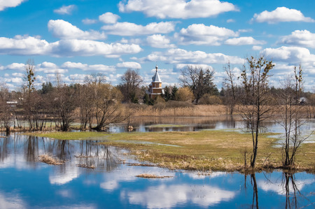 Spring high water flooded agricultural fields and trees due to flood of river against background of the village and of Orthodox Church with reflection clouds and blue sky in water in temperate zone
