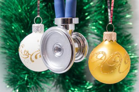 Medizinisches Weihnachten und neues Jahr. Stethoskop umgeben durch Weiß- und Goldweihnachtsbaumbälle mit unscharfer Weihnachtsdekoration auf Hintergrund - grüne Girlanden. Konzept für das neue Jahr in der Medizin Standard-Bild