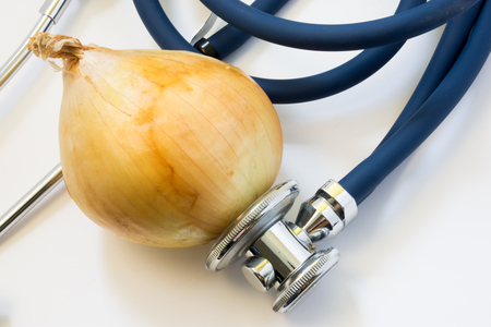 dietology: Onion and stethoscope. Stethoscope tests onion for presence of GMO, diseases of vegetable, varieties. Nutrition and health benefits of onions as organic or healthy food for health, for use in medicine