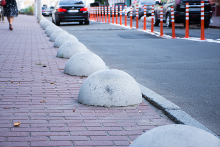 Car or motor vehicle stop security barriers or hemispheres bollards. Concrete structures to prevent parking on the sidewalks are placed at the edge of the roadway for cars