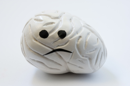 Concept photo of unhappy, sad brain with sickness disorder. Model of brain with sad smile, which symbolizes neurologic problem: discomfort, headache, ache, spasm, inflammation, migraine