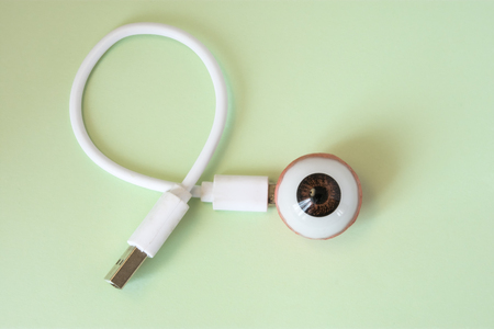 3D shape of eye ball with connected by charging cord, cable or for connecting with other devices. Concept of  technology bionic or artificial organ of eye (eyeball) for treatment or diagnosis diseases Stock Photo