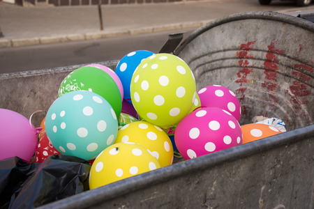 dumpster: Multi-colored polka dot balloons are in the dumpster or garbage container and on one one sits fly. Party, celebration, fun, holiday, birthday for adult or children is over or ended concept stock photo Stock Photo