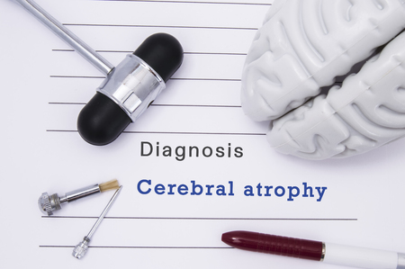 Diagnosis of Cerebral Atrophy. Neurological hammer and brain figure lie on a medical  paper form with a heading diagnosis of Cerebral Atrophy on a table in the office of a neurologist