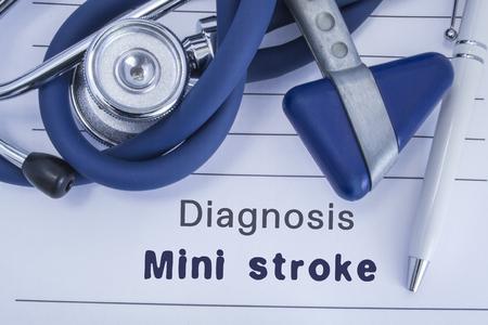 The diagnosis of mini stroke (TIA). Paper medical history with diagnosis of mini stroke, on which lie stethoscope, neurological hammer, pen. Medical concept for stroke for neurology and neuroscience Reklamní fotografie