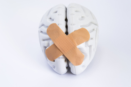 Hemispheres of human brain, stuck together using beige adhesive tape (treatment), lying on white background. Idea for visualizing brain treatment of neurological diseases such as broken brain syndrome Stock Photo