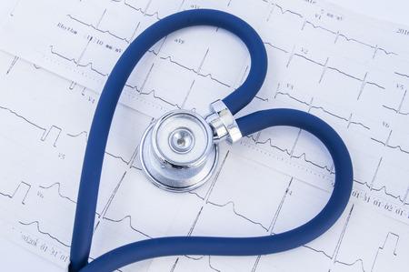 Hart gevormde stethoscoop tegen de achtergrond van elektrocardiogram (ekg). Hoofd of borststuk en flexibele buizen van blauwe stethoscoop gevouwen in hartvorm, die op afgedrukt elektrocardiogram ligt Stockfoto