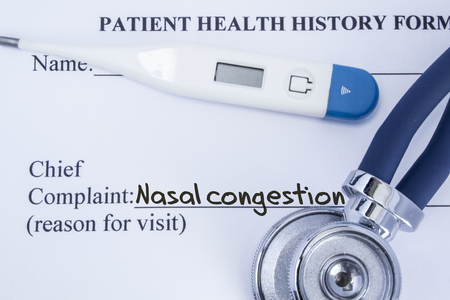 Chief complaint nasal congestion. Paper patient health history form, on which is written the complaint nasal congestion as the main reason for visit to the doctor, with a thermometer and stethoscope Stock Photo
