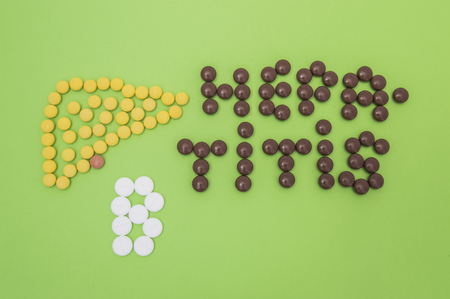 Figure or shape (contour) of human liver, composed of yellow tablets, and the diagnosis of hepatitis B sign made of yellow and white pills or tablets on a green paper background. Idea for hepatology Stock Photo