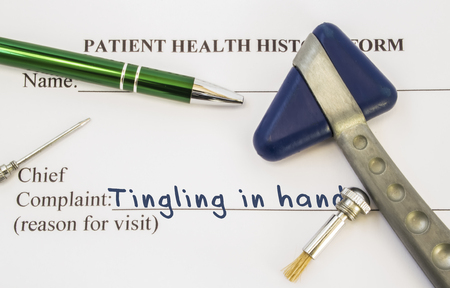 Complaint tingling in hands. Patient health history is on table of neurologist, which contains complaint tingling in hands surrounded by neurological hammer, tools to determine sensitivity of skin