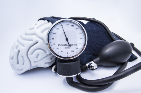 The figure of the human brain enveloped sphygmomanometer cuff with bulb (pear) and dial showing high pressure. Concept high brain or increased (raised) intracranial pressure (hypertension)