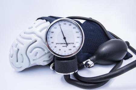 Figura ludzkiego mózgu otoczona mankietem ciśnieniomierza z gruszką (gruszką) i tarczą pokazującą wysokie ciśnienie. Koncepcja wysokiego mózgu lub podwyższonego (podwyższonego) ciśnienia wewnątrzczaszkowego (nadciśnienie)