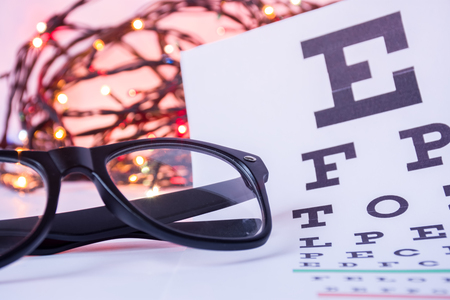 Christmas and New Year in ophthalmology optometry. Eyeglasses and ophthalmological table for visual acuity test in foreground with blurred lights bulbs Christmas garlands in background