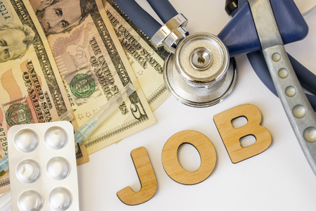 Job in medicine and pharmacy concept photo. Stethoscope, neurological reflex rubber hammer, dollar bills and syringe with medicine is near  3D letters job. Employment for doctors and pharmacists