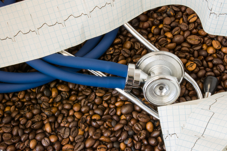 Coffee or caffeine and heart arrhythmias (irregular heartbeat). Stethoscope and ECG tape on background of coffee beans. Effect and risk of drinking coffee or caffeine on cardiac arrhythmia development