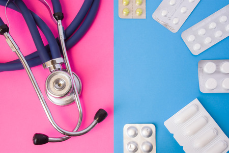 Pills, drugs, medictions and suppositories in blister package and medical stethoscope in two colors background: blue and pink. Concept of drug therapy, treatment, curing diseases of men and women Banco de Imagens